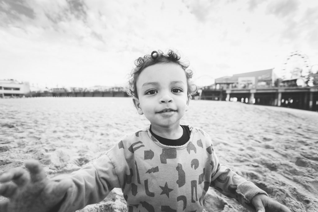 Black & white photo of a young boy on a southern California beach in Santa Monica. Family photography by Birchblaze.