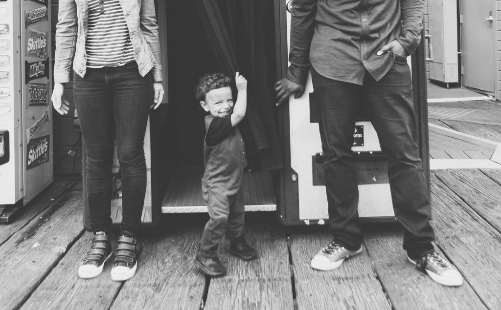B&W photo of cute little boy playing in a Santa Monica Pier photobooth with his Mom & Dad nearby. Southern California family photographers, Birch Blaze Studios.