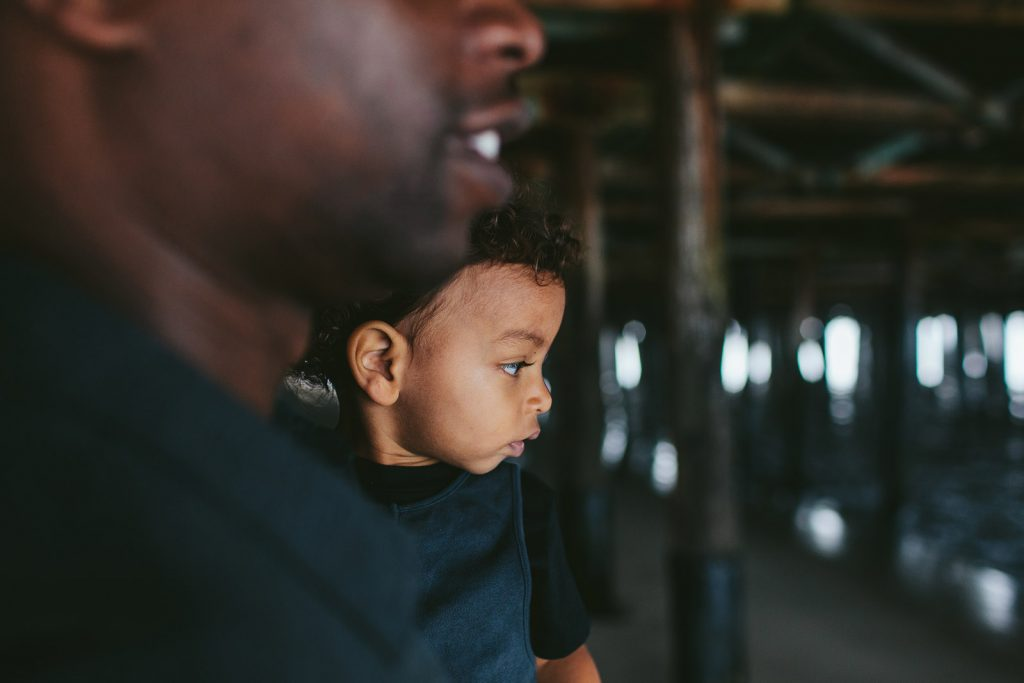 Father holding his young son under the Santa Monica Pier in Los Angeles, California. Photo by family photographers, Birch Blaze Studios.