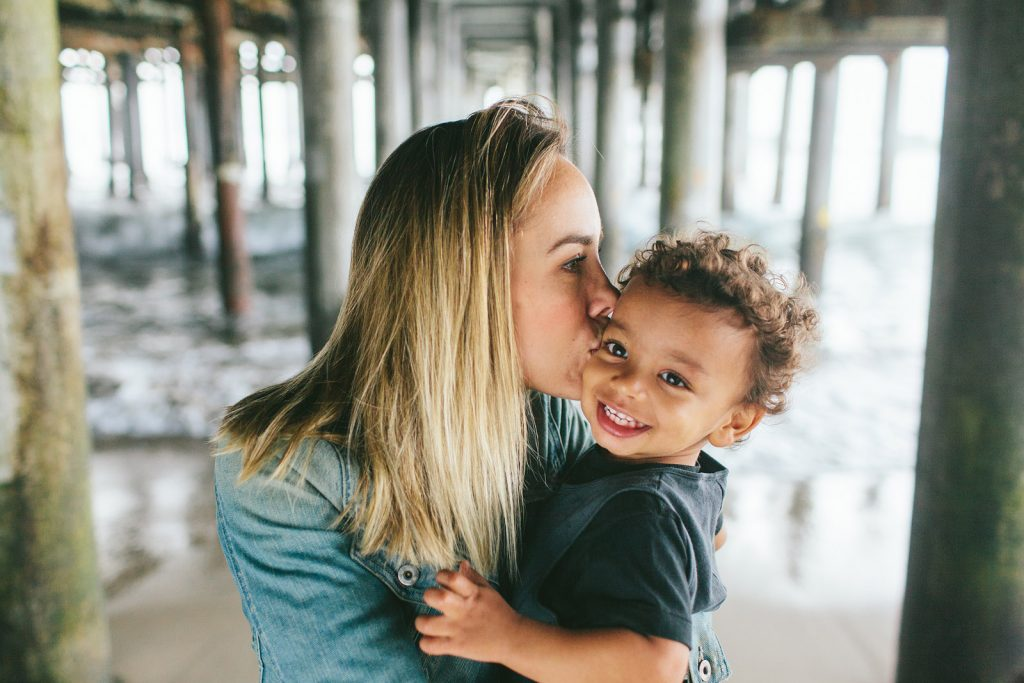 Color Photo of a mother kissing her young son under the Santa Monica Pier in southern California. Photo by Birch Blaze Studios.