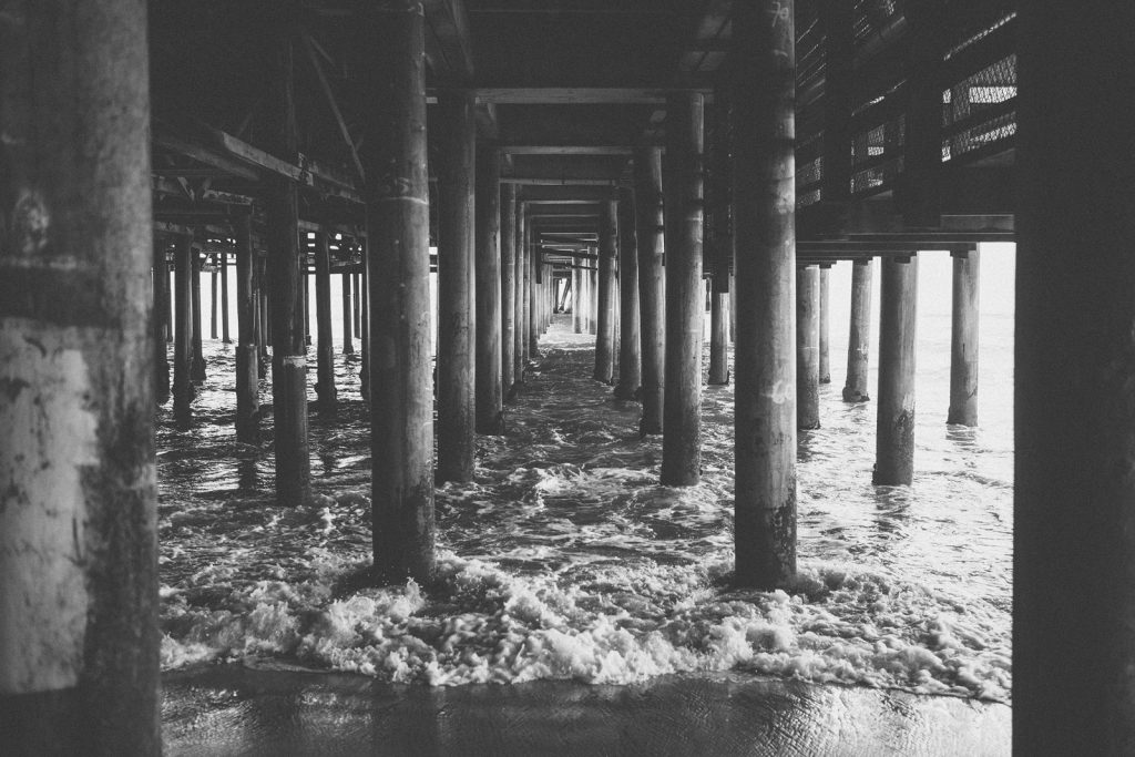 Black & white photograph of the Santa Monica Pier, taken beneath the Pier. Image by Birchblaze.