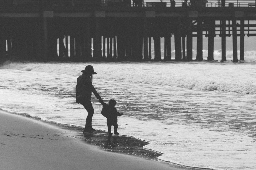 Black & white photo of the silhouettes of a  mother and young son on a southern California beach in front of the Santa Monica Pier. Family photography by Birchblaze.