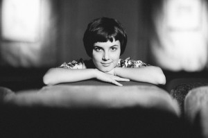Black & white portrait, young lady smiling in old theater. Short hair, dramatic lighting.