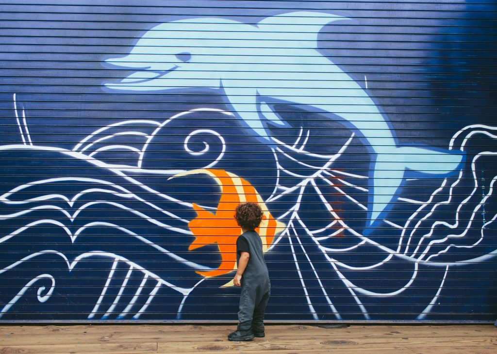 Cute little boy interested in a Santa Monica Pier marine life mural. Southern California family photographers, Birch Blaze Studios.