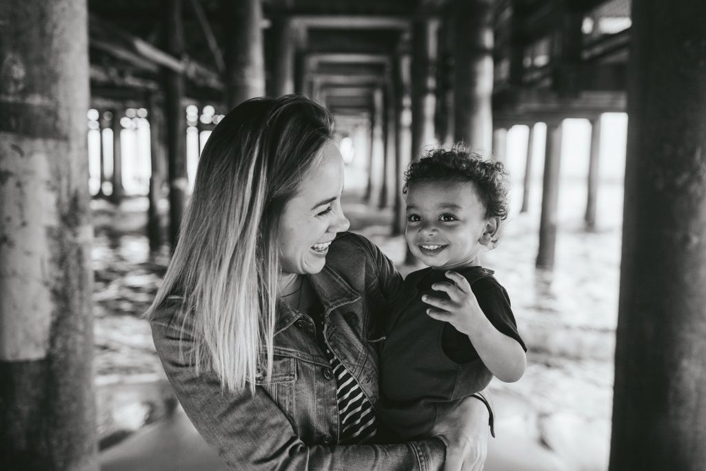 Black & White Photo of a mother and young son under the Santa Monica Pier in southern California. Photo by Birch Blaze Studios.
