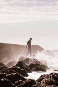 Young surfer walking on rocks. Big wave, crashing surf. Birch Blaze Studios.
