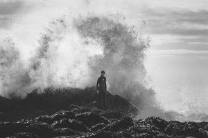 Young surfer walking on rocks. Big wave, crashing surf. Epic surf. Birch Blaze Studios.
