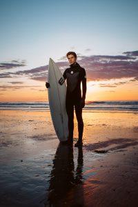 Young surfer portrait at sunrise, east coast. Hero shot. Birch Blaze Studios.