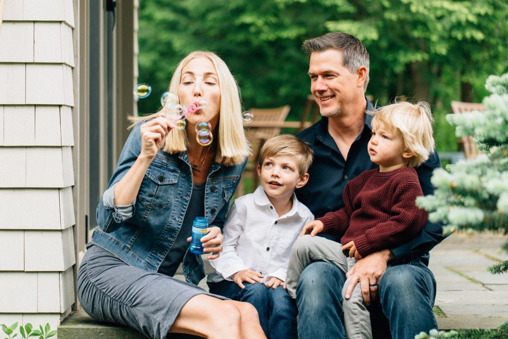 Young family blowing bubbles, Lake Winnipesaukee family photographers, Birch Blaze Studios. Wolfeboro, NH.