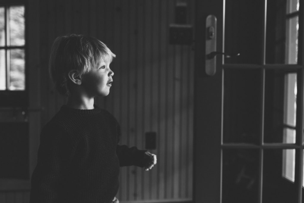 Black & white photo, little boy looking out the front door. Family lifestyle photography by Birch Blaze.