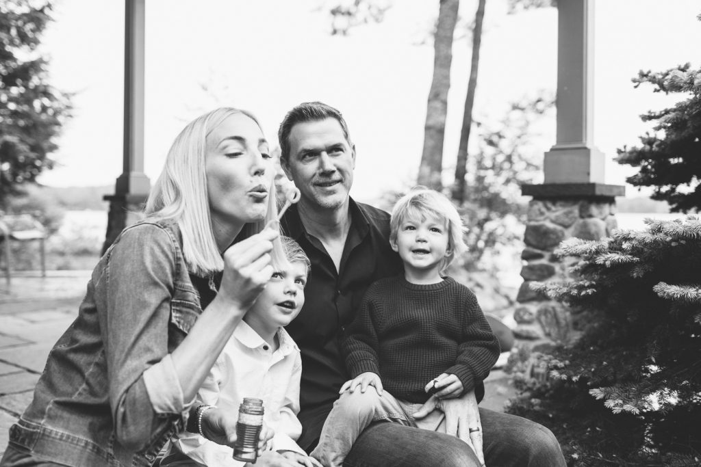 Black & White photo, young family blowing bubbles, Lake Winnipesaukee family photographers, Birch Blaze Studios. Wolfeboro, NH.