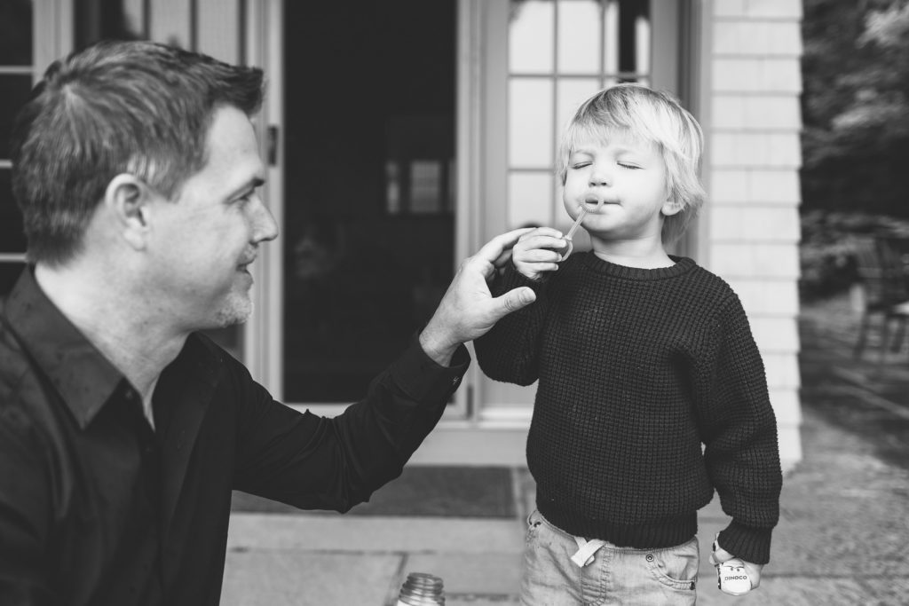 Black & white photo, little boy with his Dad, blowing bubbles. Family lifestyle photography by Birch Blaze.