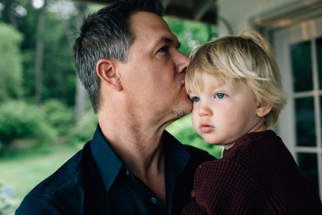 Dad kissing young son. Lake Winnipesaukee family portrait photographers, Birch Blaze Studios.