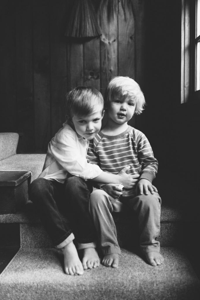 Black & white photo of 2 young brothers hugging, Lake Winnipesaukee family photographers, Birch Blaze.