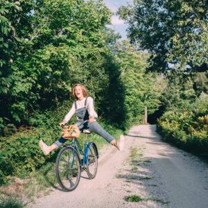 Young woman's senior portrait session in Jackson, NH. Girl riding a vintage bicycle. Senior photos in the White Mountains by Birch Blaze Studios. © 2021 Birch Blaze Studios.